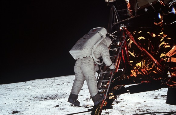 Astronaut backing down a short ladder, gold covered body of lander to right, white landscape and black sky.