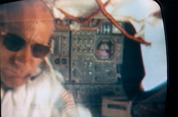 Blurry man's face with sunglasses on left, panel with many controls visible behind him.