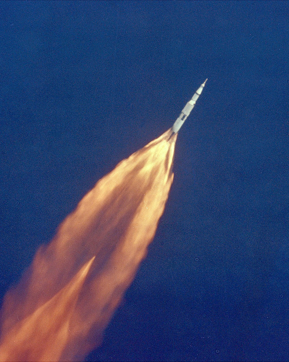 Distant ascending rocket with vast tail of orange flame.