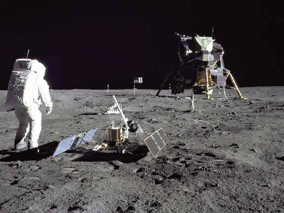 Astronaut in foreground with complicated device on the ground, lunar lander and flag in background.