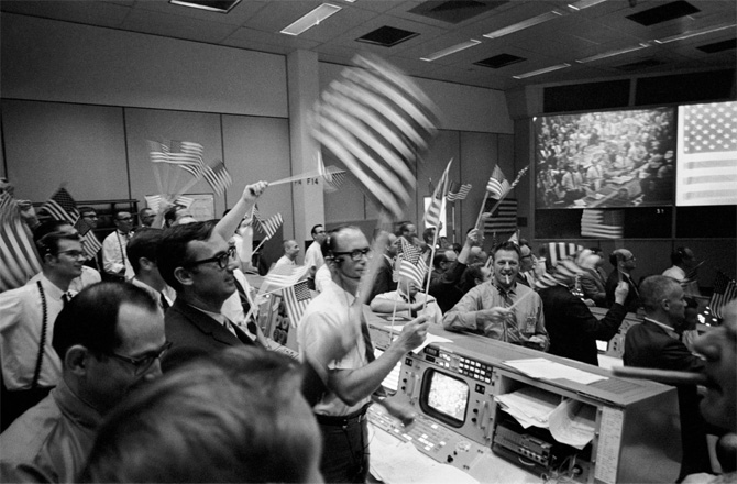 Roomful of exhilarated men standing and waving American flags, control panels visible.