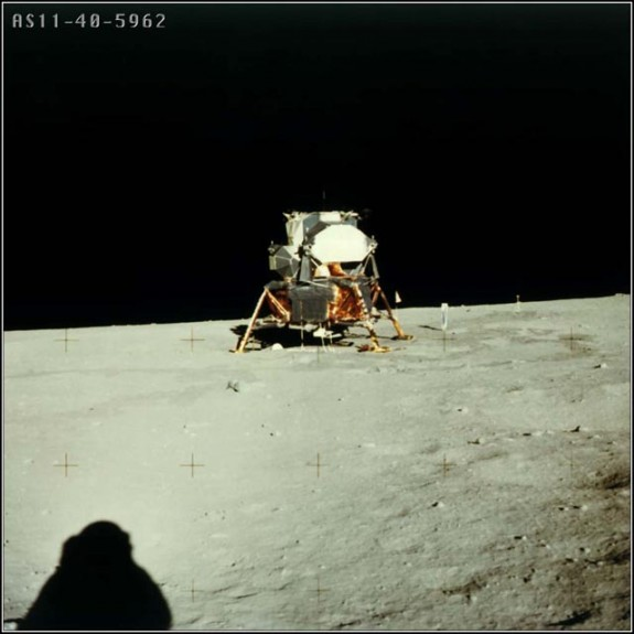 Sunny side of boxy spacecraft on bent legs in distance, with astronaut's shadow on the ground.
