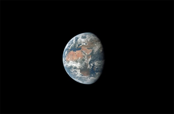Earth, more than half lit, hanging in space with Africa and the Middle East visible through clouds.