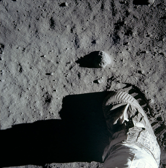 View straight down onto moon boot hovering over partly visible ridged boot print.