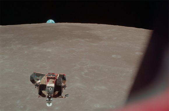 Boxy spacecraft in middle distance high above lunar surface, with Earth peeking up over the horizon.