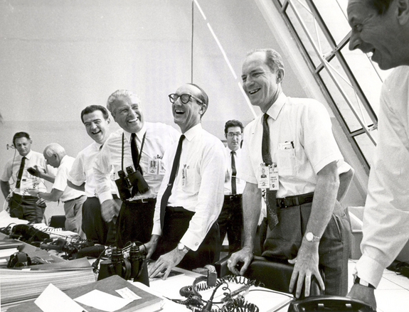Eight happy, laughing men in white shirts with dark ties standing by control panels.