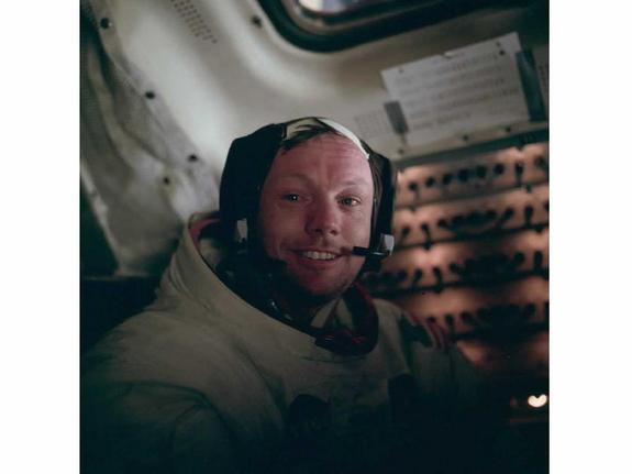 Boyish looking man in space suit with helmet off grinning at the camera.