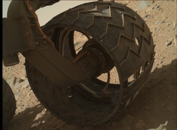 View larger. | A puncture (center right) in one of the Mars rover Curiosity's wheels. (The sequence of cutouts at lower right are deliberate and imprint 'JPL' in Morse code as the wheels roll across the Martian surface.)  Image via NASA/JPL-CALTECH/MSSS, Nature.