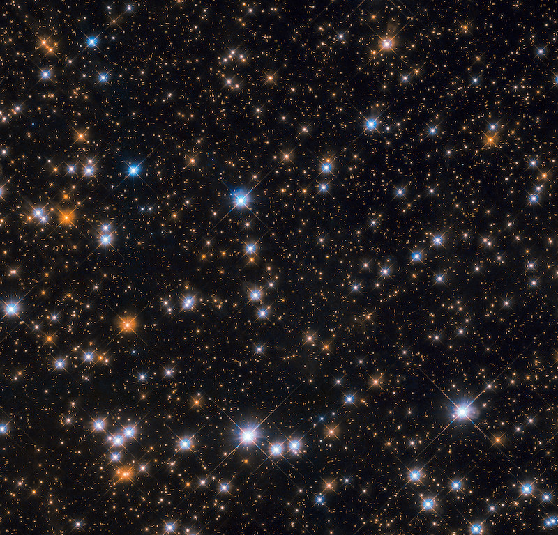 A star field showing a small section of Messier 11, with white, blue, and red stars.