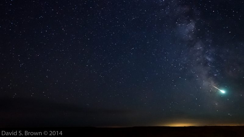 Starry sky with Milky Way visible and fuzzy bright green dot with short glowing trail near horizon.