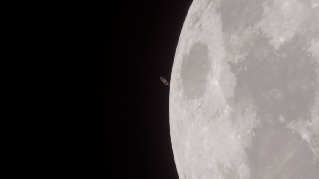 Partial moon with tiny, dim, ringed Saturn next to it.