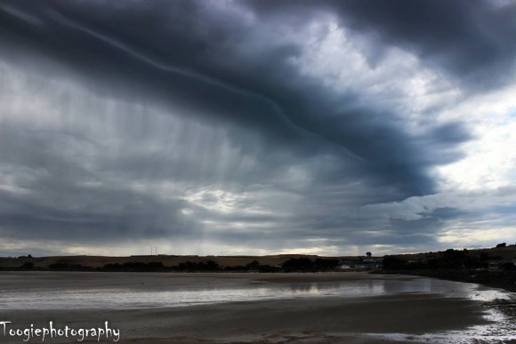 Shelf cloud above a beach.
