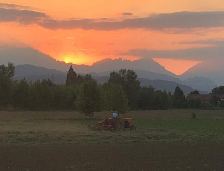 Glorious orange sky behind receding blue hills, man on tractor in foreground.
