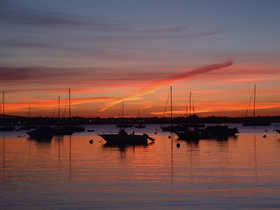 Slate sky, orange clouds reflected in calm sea with anchored sailboats.