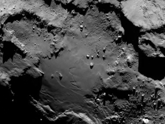 Stunning close up detail focusing on a smooth region on the base of the 'body' section of Comet 67P/Churyumov-Gerasimenko. The image was taken by Rosetta's OSIRIS narrow-angle camera from a distance of 130 km and downloaded on August 6, 2014. The image clearly shows a range of features, including boulders, craters and steep cliffs.