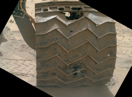 View larger. | Curiosity rover's left front wheel at Sol 713 - that is, 713 Martian days since the rover touched down on Mars in 2012.