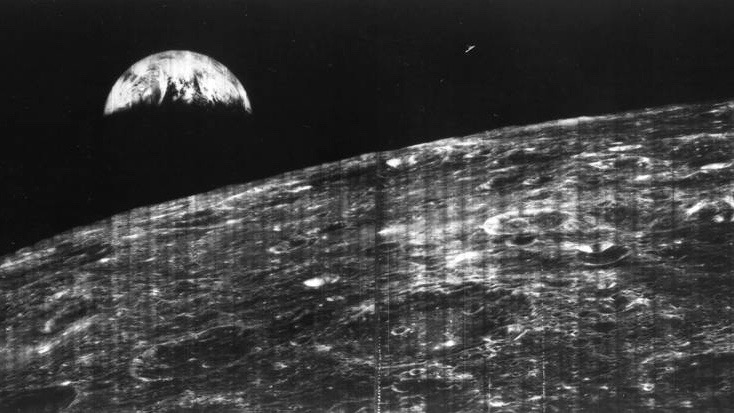 Fuzzy black and white view of crescent Earth in black sky over orbital view of lunar landscape.