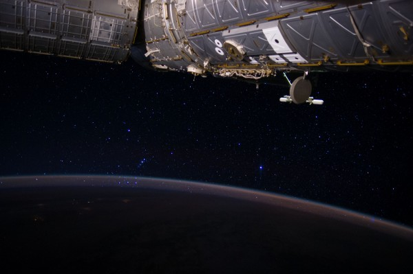 Space station components above with night sky over orbital view of curve of Earth.