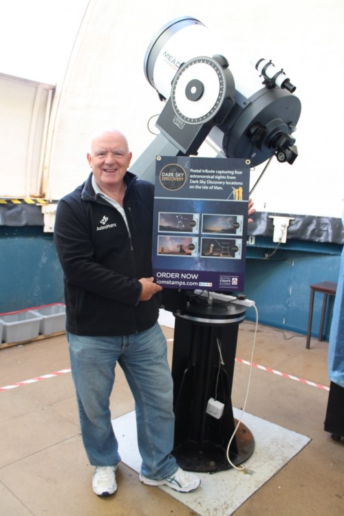 Howard Parkin at the Isle of Man Observatory with a poster of the stamps.  Photo via Isle of Man Post Office.