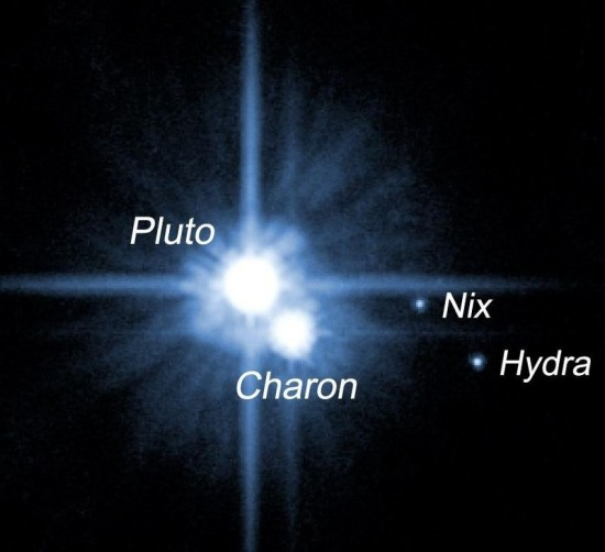 This 2005 image shows Pluto and four of its five known moons.  Image via HubbleSite
