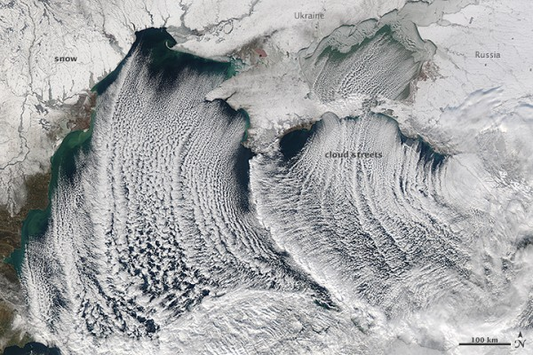 Very many curved parallel lines of clouds seen from orbit in black and white.