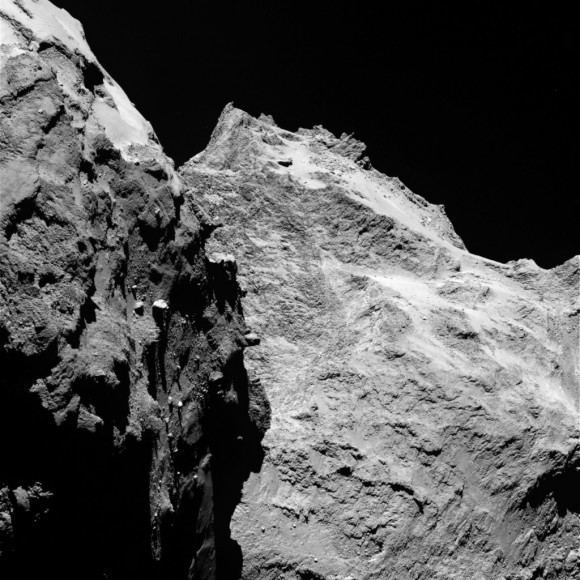 Jagged cliffs and prominent boulders are visible in this image taken by Rosetta's OSIRIS imaging system on September 5, 2014 from a distance of 62 kilometers from comet 67P/Churyumov-Gerasimenko. The left part of the image shows a side view of the comet's 'body,' while the right is the back of its 'head'. One pixel corresponds to 1.1 meters. Image via ESA/Rosetta/MPS for OSIRIS Team MPS/UPD/LAM/IAA/SSO/INTA/UPM/DASP/IDA