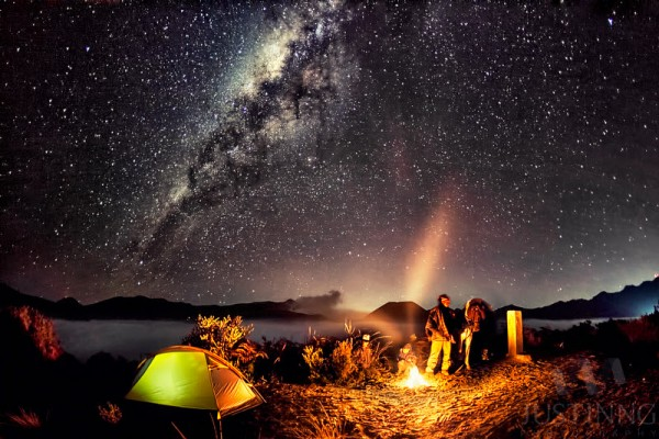 Campfire under the Milky Way galaxy by Justin Ng.
