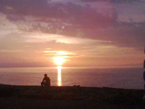 Silhouette of a man seated on a beach, watching sunset over an ocean.
