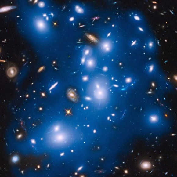 Massive galaxy cluster Abell 2744, nicknamed Pandora's Cluster, takes on a ghostly look where total starlight has been artificially colored blue in this Hubble view.  Image via NASA/ESA/IAC/HFF Team, STScI