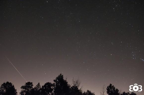 Starry sky, treetops below, diagonal bright streak in lower left corner.