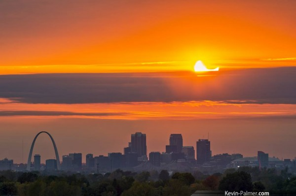 A partially eclipsed sun sets over the skyline of Saint Louis, Missouri by Kevin Palmer Photography