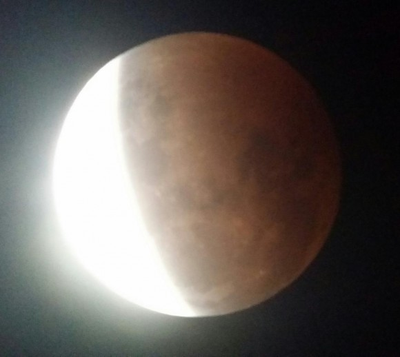 As the eclipse deepens, you could begin to see some subtle colors in the shadowed portion of moon.  Photo by Chris Calubaquib (@ChrisAstro on Twitter)