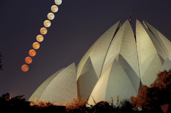 Ascending line of full moons above multiple overlapping crescent-shaped roofs of large structure.