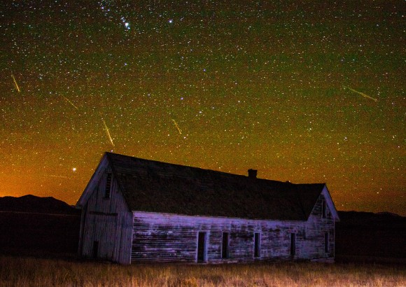 An old frame house under a starry sky with many bright streaks of meteors.
