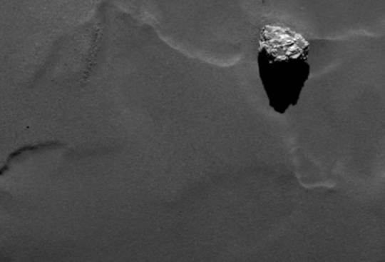 Close-up of the boulder Cheops as it casts a long shadow on the surface of comet 67P/Churyumov-Gerasimenko. Image via ESA/Rosetta/MPS for OSIRIS Team MPS/UPD/LAM/IAA/SSO/INTA/UPM/DASP/IDA