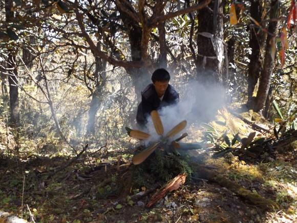 Renzin Dorji burning juniper and rhododendron as an offering at the pass of Ko-la.  Photo credit: Ben Orlove