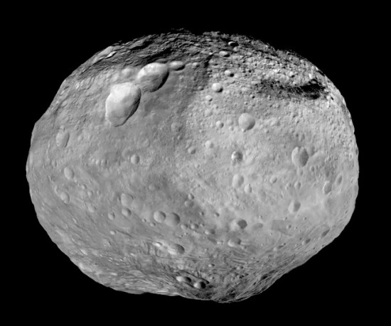 Dawn studied Vesta from July 2011 to September 2012. The towering mountain at the south pole — more than twice the height of Mount Everest — is visible at the bottom of the image. The set of three craters known as the