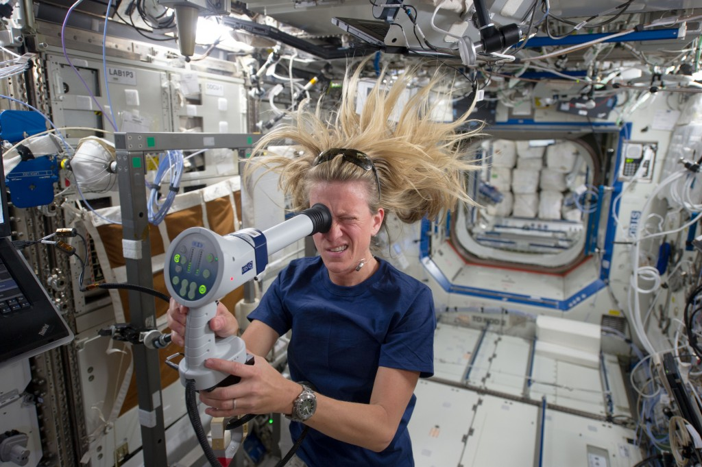 An astronaut with long hair floating in the air on board the ISS holds a device to her eye.