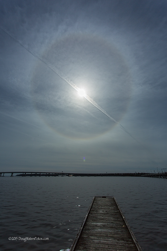 Brilliant sun with halo bisected by long, thin line of cloud over river with dock.