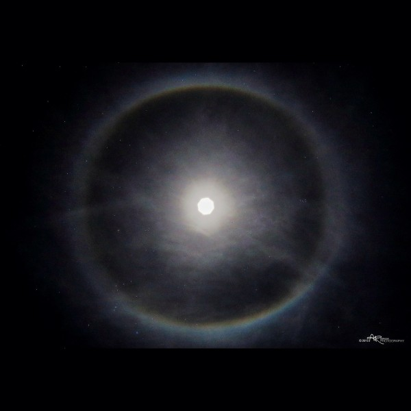 Bright moon in dark sky with bright halo and wispy clouds.