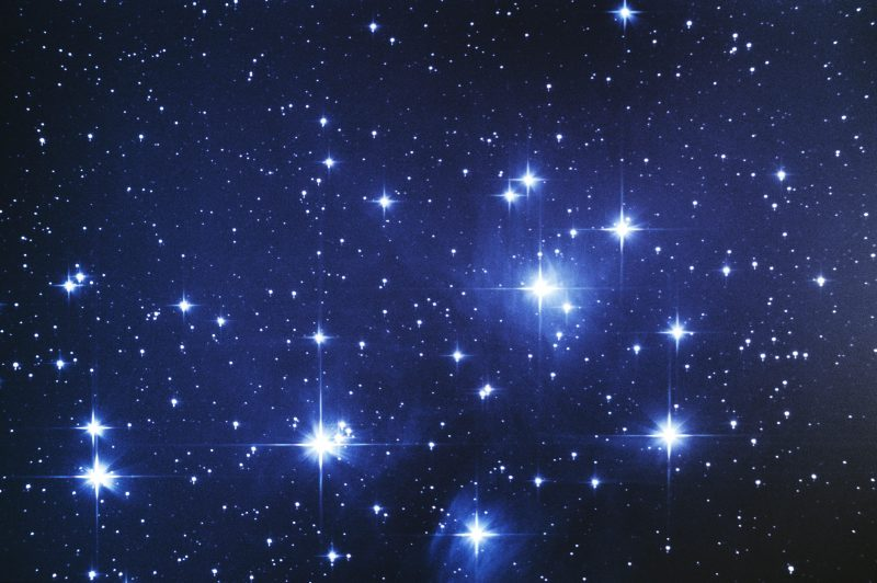 Closeup of numerous close together bright stars in glowing blue clouds.