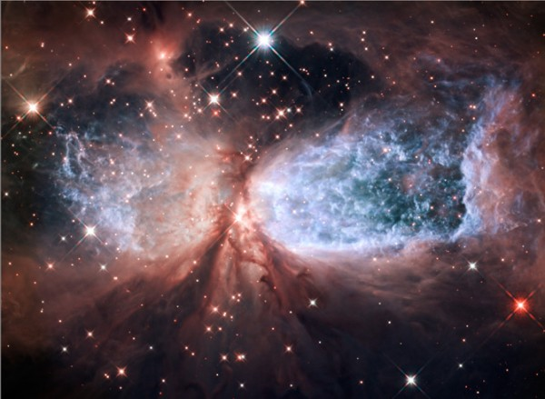 The bipolar star-forming region, called Sharpless 2-106, looks like a soaring, celestial snow angel. Credit: NASA, ESA, and the Hubble Heritage Team (STScI/AURA)  Read more about this image.