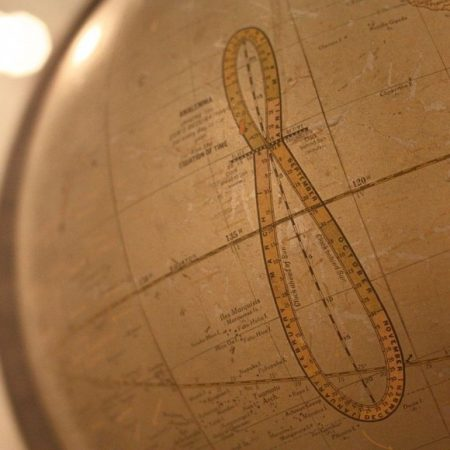 Globe with large vertical figure 8 with intervals marked on it.