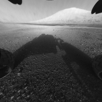View larger. | Curiosity's shadow in the foreground, Mount Sharp in the background.  Read more about this image.