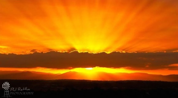 Symmetrical blazing orange and yellow sunset with dark rays converging to a point behind a cloud.