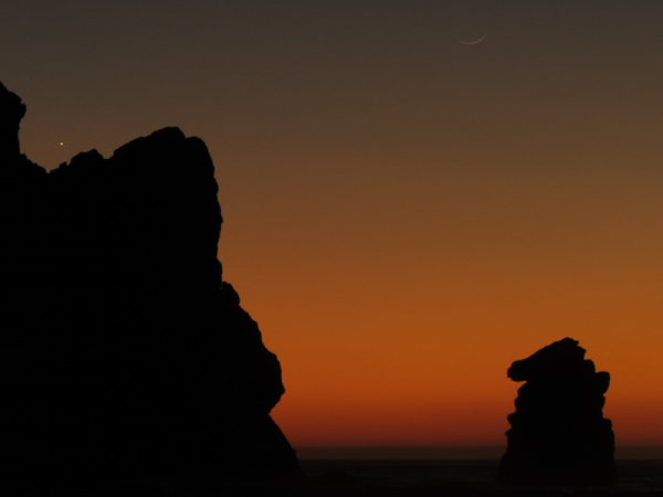 Venus above the rocks, moon in the upper right of photo, by Spencer Mann, at Morro Bay, California.