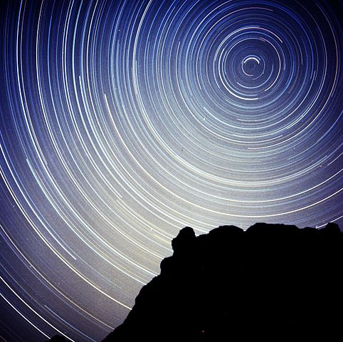 View larger. The stars revolve around the North Star, which serves as the center of the great celestial clock.  Star trails produced by long time exposure photograph.
