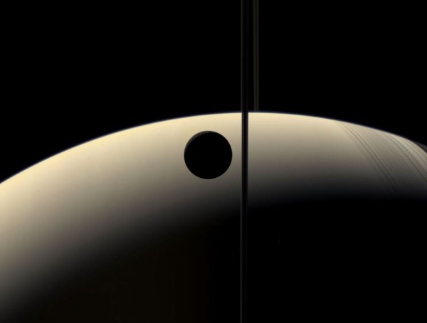 Crescent moon Rhea occults - or passes in front of - a crescent Saturn, as seen by the orbiting Cassini spacecraft.  Image via Cassini Imaging Team, SSI, JPL, ESA, NASA.