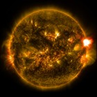 An M-class solar flare erupts from the right side of the sun in this image from shortly before midnight EST on Jan. 12, 2015. The image blends two wavelengths of light -- 171 and 304 angstroms -- as captured by NASA's Solar Dynamics Observatory. Image via NASA/SDO