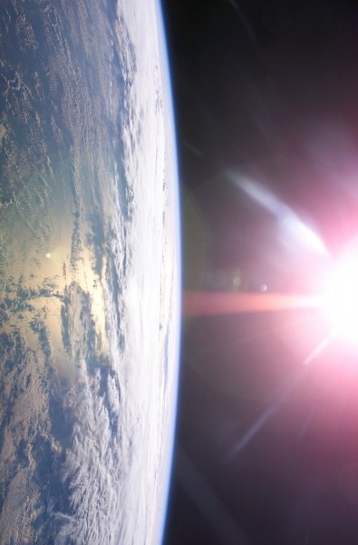 Earth and sun via ISS Expedition 13 / NASA.